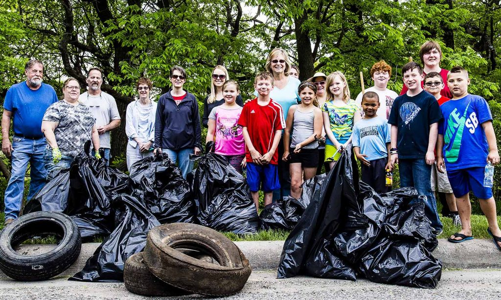 Mary Aney and her Roots & Shoots Youth Volunteer Group present the mound of trash they pulled up. Some FPNA folks snuck in as well