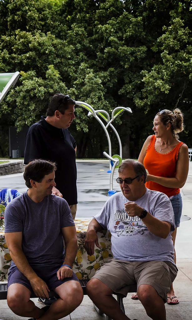 Mark and Shari Hanson take a quick break from setting up the picnic while John and Greg are deep in conversation